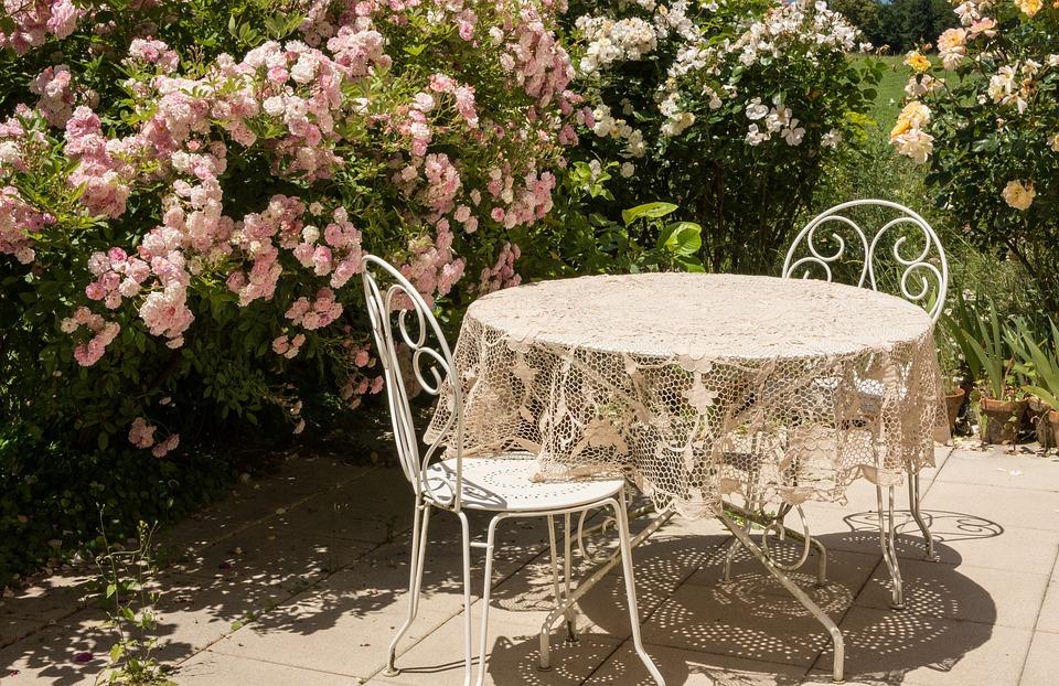 Hyggelig terrasse med bord, stole og blomster